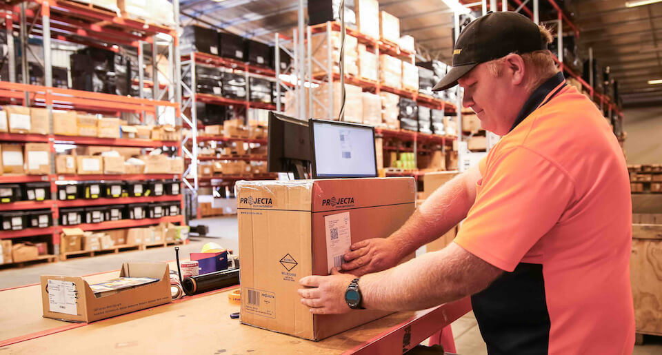 Man in warehouse using Neto ecommerce Pick'n Pack to fulfil orders and label box